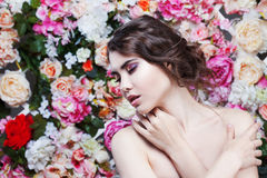 Portrait of  beautiful fashion girl, sweet, sensual. Beautiful makeup and messy romantic hairstyle. Flowers background Stock Photos