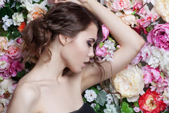 Portrait of  beautiful fashion girl, sweet, sensual. Beautiful makeup and messy romantic hairstyle. Flowers background Royalty Free Stock Photos