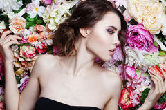 Portrait of  beautiful fashion girl, sweet, sensual. Beautiful makeup and messy romantic hairstyle. Flowers background. Royalty Free Stock Photography