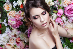 Portrait of beautiful fashion girl, sweet, sensual. Beautiful makeup and messy romantic hairstyle. Flowers background. Stock Images