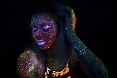 Portrait of Beautiful Fashion Woman in Neon UF Light. Model Girl with Fluorescent Creative Psychedelic MakeUp, Art Stock Image