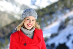 Woman smiling looking at you in winter. Portrait of a beautiful fashion woman smiling looking at you in a snowy mountain in winter Royalty Free Stock Photo