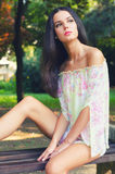 Portrait of the beautiful fashionable girl sitting on the bench in spring Royalty Free Stock Photos