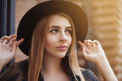 Portrait of beautiful fashionable girl wearing stylish wide-brimmed black hat looking up. City lifestyle. Toned Royalty Free Stock Photography