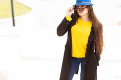 Portrait of a beautiful fashionable stylish woman in bright yellow sweater and blue hat. Street style shooting royalty free stock image