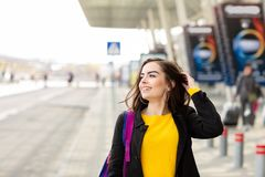 Portrait of a beautiful fashionable stylish woman in bright yellow sweater. Street style shooting stock image