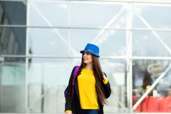 Portrait of a beautiful fashionable stylish woman in bright yellow sweater. Street style shooting royalty free stock photo