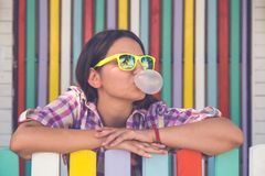 Young female leaning on fence and chewing gum royalty free stock images