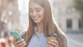 Portrait of Beautiful Fashionable Young Woman with Brown Hair and Headband Wearing Striped Shirt Using her Smartphone stock video