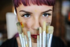 Portrait of beautiful female artist with purple hair and dirty h. Close up portrait of beautiful female artist with purple hair and dirty hands with different royalty free stock image