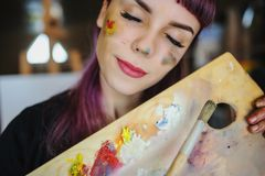 Portrait of beautiful female artist with purple hair and dirty h. Close up portrait of beautiful female artist with purple hair and dirty hands with different stock photo