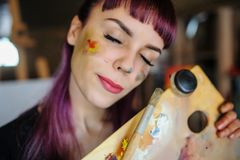 Portrait of beautiful female artist with purple hair and dirty h. Close up portrait of beautiful female artist with purple hair and dirty hands with different royalty free stock photos