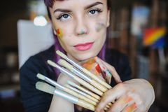 Portrait of beautiful female artist with purple hair and dirty h. Close up portrait of beautiful female artist with purple hair and dirty hands with different stock images