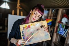 Portrait of beautiful female artist with purple hair and dirty h. Close up portrait of beautiful female artist with purple hair and dirty hands with different stock photos