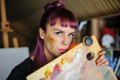 Portrait of beautiful female artist with purple hair and dirty h. Close up portrait of beautiful female artist with purple hair and dirty hands with different stock image