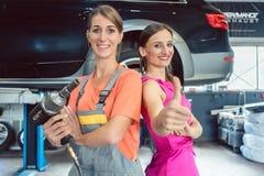 Portrait of a beautiful female auto mechanic next to her happy customer stock photos