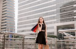 Portrait of beautiful female in black dress smling and holding shopping bags in city stock images