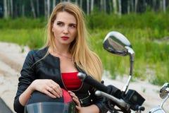 Portrait beautiful female blond biker on motorcycle Stock Image