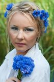 Portrait of beautiful female with blue flowers Royalty Free Stock Photography