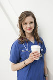 Portrait of a beautiful female doctor holding a disposable cup over colored background Stock Images