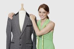 Portrait of beautiful female dressmaker standing with tailor's dummy over gray background Royalty Free Stock Photography