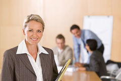 Portrait of beautiful female executive. With co-workers in the background Stock Images