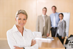 Portrait of beautiful female executive. With co-workers in background Stock Images