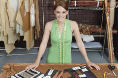 Portrait of beautiful female fashion designer standing at table with layouts Stock Photos