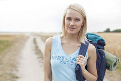 Portrait of beautiful female hiker with backpack standing on field Royalty Free Stock Images