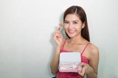 Portrait of beautiful female model holding make-up brushes Set royalty free stock photos