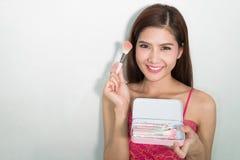 Portrait of beautiful female model holding make-up brushes Set Royalty Free Stock Photography