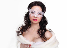 Portrait of a beautiful female model with mask in fur coat on white background stock photo