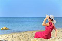 Portrait of beautiful female in red dress on beach Royalty Free Stock Photo