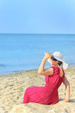 Portrait of beautiful female in red dress on beach Royalty Free Stock Image