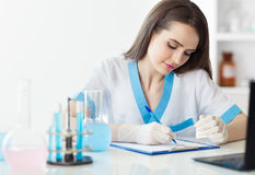 Portrait of beautiful female scientist writing notes Stock Image