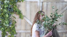 Portrait of a beautiful florist girl with a eucalyptus branch against a wooden gate decorated with flowers stock photo