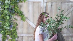 Portrait of a beautiful florist girl with a eucalyptus branch against a wooden gate decorated with flowers