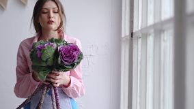 Portrait of a beautiful florist with a violet bouquet of unusual flowers - brassica. Look in the camera. 4k stock video