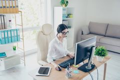 Portrait of beautiful focused asian young businesswoman sitting at bright modern work station and typing on laptop. Attractive cha. Rming serious concentrated stock photo