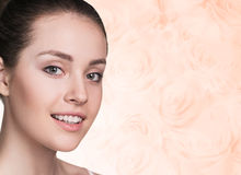 Portrait of beautiful, fresh, healthy woman. Close-up portrait of beautiful, fresh, healthy and sensual girl over soft roses background royalty free stock images