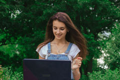 Portrait of a beautiful fun brunette sitting on a street with a laptop Stock Images