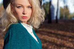 Portrait of beautiful fun happy blond girl in a hat in autumn forest Stock Photos