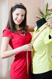 Portrait of beautiful funny young pinup woman in red dress with measuring tape & mannequin happy smiling & looking in camera Royalty Free Stock Image