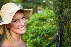 Portrait of beautiful gardener using hedge clippers at garden Royalty Free Stock Photography