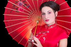 Portrait of beautiful geisha in red japanese dress with umbrella. Close up portrait of beautiful geisha in red japanese dress with umbrella Stock Photo