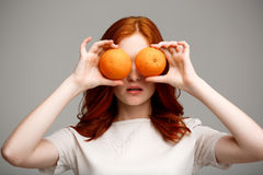 Portrait of beautiful ginger girl holding oranges over gray background. Royalty Free Stock Photography