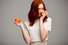 Portrait of beautiful ginger girl holding oranges over gray background. Stock Photo