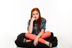 Portrait of beautiful ginger girl sitting crosslegged over white background. Portrait of young beautiful ginger girl sitting, looking at camera over white Stock Photo
