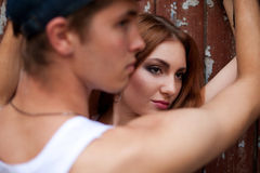 Portrait of a beautiful ginger girl standing with a man over woo stock photo
