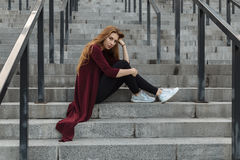 Portrait of beautiful ginger hair girl in a coat with red lips posing by the street in a city looking at camera and Stock Photos